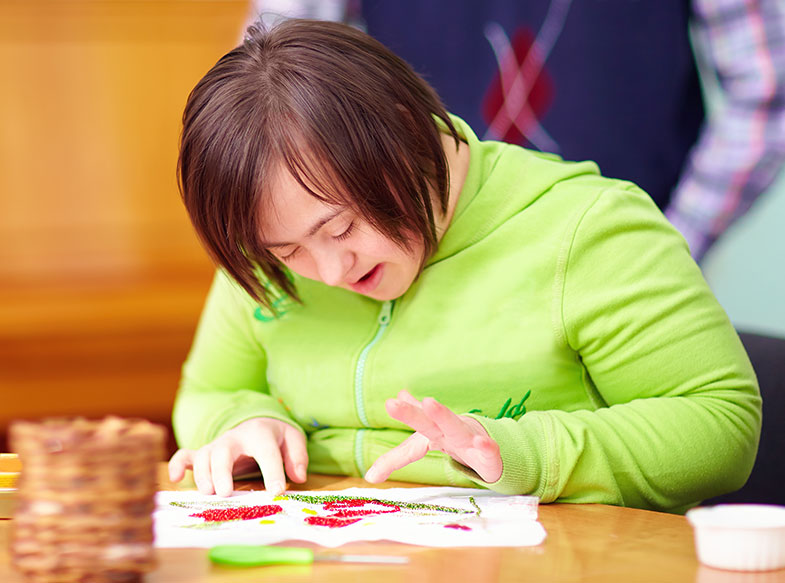 Girl sitting at a desk finger painting