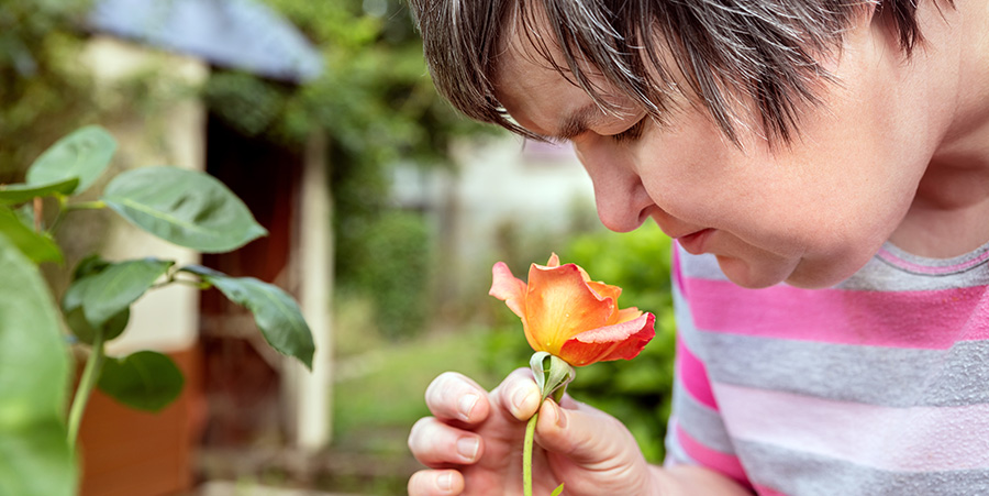 Handicapped person smelling a flower